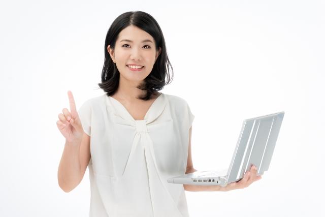 パソコンを持って指差しする女性