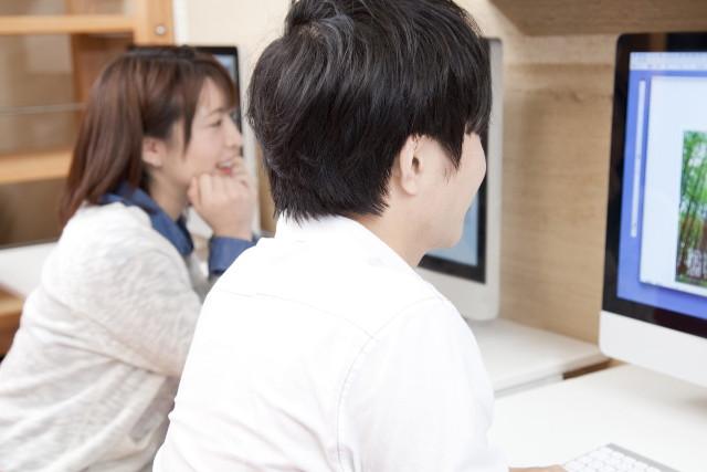 パソコンを見る二人の若い男女